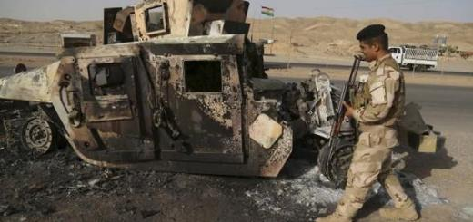 A Kurdish Peshmerga soldier walks past the wreckage of a burnt vehicle belonging to Iraqi security forces on a road in the town of Sulaiman Pek